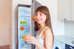 Young brunette girl with a glass of juice near the refrigerator Royalty Free Stock Images