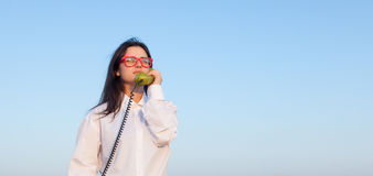 Young brunette girl with green dial handset Royalty Free Stock Photos
