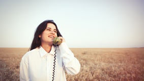 Young brunette girl with green dial handset Royalty Free Stock Image