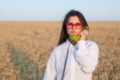 Young brunette girl with green dial handset Royalty Free Stock Photography