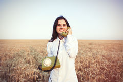 Young brunette girl with green dial handset Stock Photos