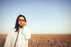 Young brunette girl with green dial handset Stock Images