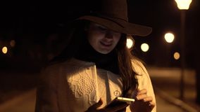Young brunette girl in a hat walks at night park and starts to check her phone stock video