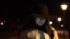 Young brunette girl in a hat and white coat walks at night park starts to check her phone and smiles stock footage
