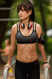 Young brunette girl with headphones doing exercise on parallel bars Stock Photo