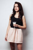 Young brunette girl with her hair in a pretty pink skirt holding Royalty Free Stock Image