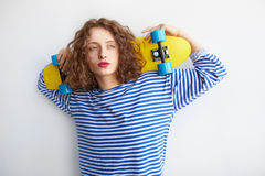 Young brunette girl in hipster clothes holding colorful skateboard Stock Photo