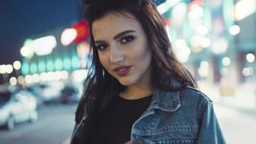 Young brunette girl in jeans jacket and stylish hairstyle, with red lips wondering in the night city, turns to the stock video footage
