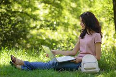 Young brunette girl with laptop outdoors is working Royalty Free Stock Photography