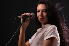 Young brunette girl with long hair with a microphone stock photos