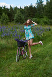 A young brunette girl lupine meadow. The girl with a bouquet of lupine and bike sunny summer day lupine field Stock Photography