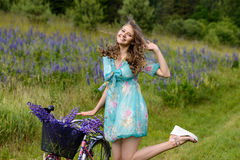 A young brunette girl lupine meadow. The girl with a bouquet of lupine and bike sunny summer day lupine field Royalty Free Stock Photo