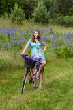 A young brunette girl lupine meadow. The girl with a bouquet of lupine and bike sunny summer day lupine field Royalty Free Stock Images