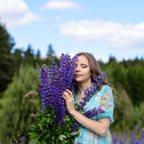 A young brunette girl lupine meadow. The girl with a bouquet of lupines lupine sunny summer day outdoors Stock Photos