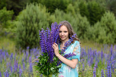 A young brunette girl lupine meadow. The girl with a bouquet of lupines lupine sunny summer day outdoors Royalty Free Stock Photos