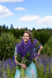 A young brunette girl lupine meadow. The girl with a bouquet of lupines lupine sunny summer day outdoors Royalty Free Stock Photo