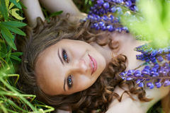 A young brunette girl lupine meadow. Girl lie lupine meadow sunny summer day Stock Images