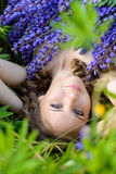 A young brunette girl lupine meadow. Girl lie lupine meadow sunny summer day Royalty Free Stock Images