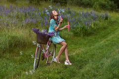 A young brunette girl lupine meadow. Girl lupine outdoors sitting on bicycle blowing soap bubbles on a sunny summer day Stock Images