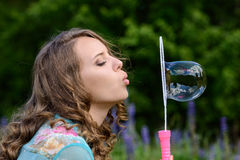 A young brunette girl lupine meadow. Girl lupine outdoors sitting on bicycle blowing soap bubbles on a sunny summer day Stock Photo