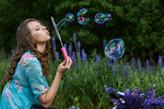 A young brunette girl lupine meadow. Girl lupine outdoors sitting on bicycle blowing soap bubbles on a sunny summer day Royalty Free Stock Photography