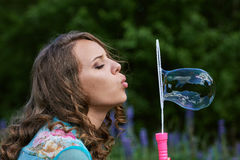 A young brunette girl lupine meadow. Girl lupine outdoors sitting on bicycle blowing soap bubbles on a sunny summer day Stock Photography