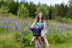 A young brunette girl lupine meadow. Girl in a white hat and the bike sunny summer day lupine field Royalty Free Stock Photo