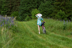 A young brunette girl lupine meadow. Girl in a white hat and the bike sunny summer day lupine field Stock Photos