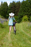 A young brunette girl lupine meadow. Girl in a white hat and the bike sunny summer day lupine field Royalty Free Stock Photography