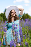 A young brunette girl lupine meadow. The girl with a white hat lupine field on a sunny summer day Royalty Free Stock Image