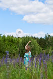 A young brunette girl lupine meadow. The girl with a white hat lupine field on a sunny summer day Stock Photography