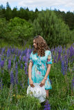 A young brunette girl lupine meadow. The girl with a white hat lupine field on a sunny summer day Stock Photos