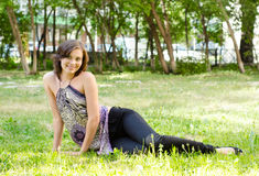 Young brunette girl lying in grass Royalty Free Stock Photography
