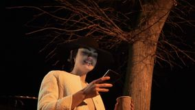 Young brunette girl at night in a hat looks at the phone and drinks coffee under the tree stock video footage
