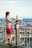 Young brunette girl observing cityscape with a Tourist Sightseeing Binoculars Royalty Free Stock Photography