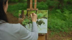 A young brunette girl paints a picture in the forest. Landscape with oil paints on canvas. A young brunette girl paints a picture in the forest. She paints a stock video