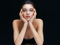 Young brunette girl with perfect make up. On black background. Youth and skin care concept stock images