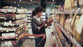 Young brunette girl picks out two packs of macaroni or pasta at local grocery store. Shopping push cart full of products