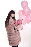 Young brunette girl in pink fur coat with rose bouquet of flower Royalty Free Stock Photo