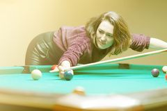 The girl is playing billiards royalty free stock photography