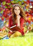 Young brunette girl reading a book. Portrait of beautiful young brunette girl reading a book in the park at fall Royalty Free Stock Photos
