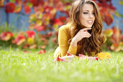 Young brunette girl reading a book. Portrait of beautiful young brunette girl reading a book in the park at fall Royalty Free Stock Photo