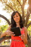 Young brunette girl reading E-book at park. Young brunette girl reading E-book at park, close-up Stock Image