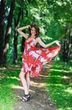 A young brunette girl in a red dress is dancing on an avenue in a summer park against a backdrop of trees Stock Photography