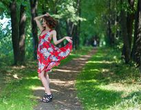 A young brunette girl in a red dress is dancing on an avenue in a summer park against a backdrop of trees Stock Image