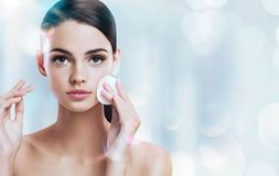 Young brunette girl removing makeup from her face. royalty free stock photography
