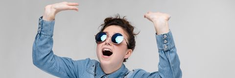 Young brunette girl in round glasses. Hairs are gathered in a bun. The girl lifted her hand up. Young girl in round glasses on a gray background. Portrait of a royalty free stock photo