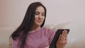 Young Brunette Girl Sits On Leather Sofa at Home And Working On Tablet stock video