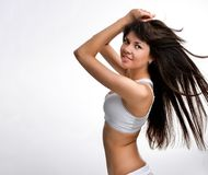 Young brunette girl is standing sideways and looking at the camera. long hair develops, girl in studio royalty free stock photo