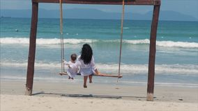 Young brunette girl swings on a beach swing with her son. Have fun on summer vacation. Beautiful Happy woman enjoying on stock video